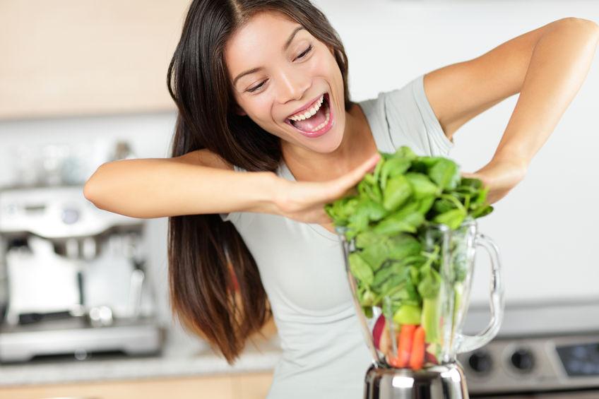 Frau bereitet grünen Smoothie mit Standmixer zu